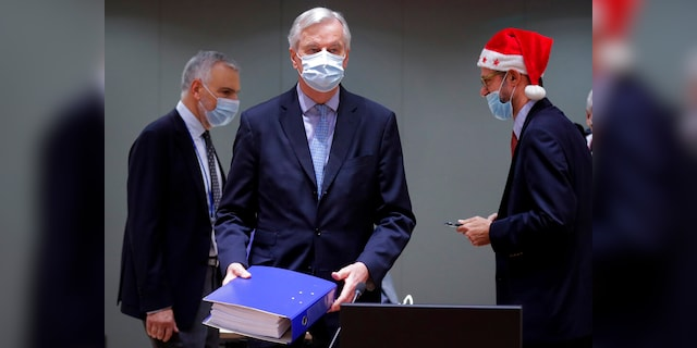 A colleague wears a Christmas hat while the chief EU negotiator, Michel Barnier, in the center, holds a file of a trade agreement for Brexit during a special meeting of Coreper, at the European Council building in Brussels, on December 25 (AP)