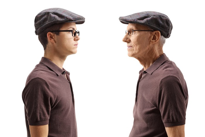 An old man looks at a young man wearing identical clothes